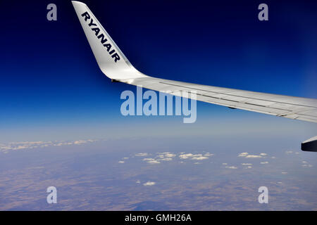 Ryanair plane wing-tip flying over southern Portugal - Stock Photo