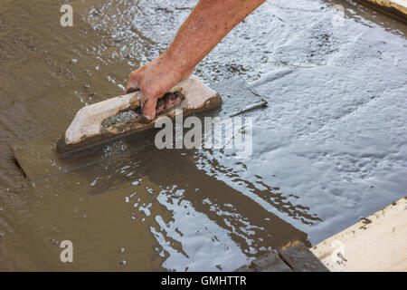 hand spreading poured concrete and leveling concrete with trowel - Stock Photo