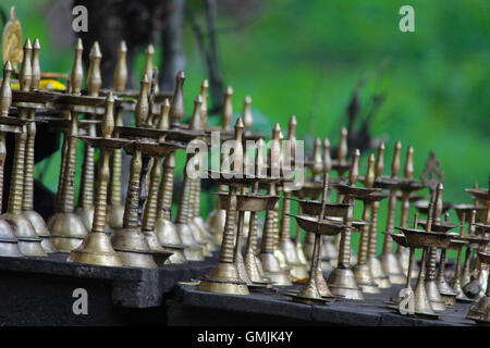 Group of brass temple lamps (Indian oil lamp) in green background. - Stock Photo