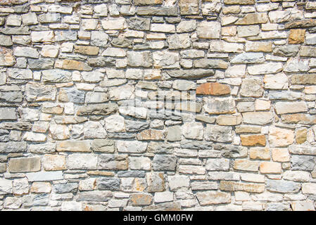 Close up of an ancient stone wall. Stone wall background. - Stock Photo