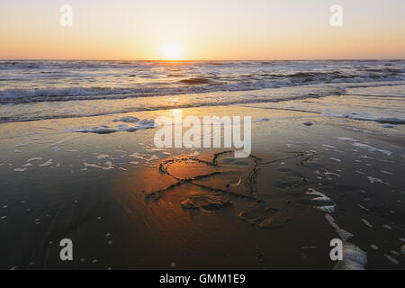 Figure heart pierced by an arrow drawn on the sandy beach lapped by the waves. - Stock Photo