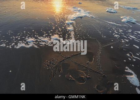 Heart pierced by an arrow drawn on the sandy beach lapped by the waves. - Stock Photo