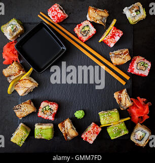 Traditional Japanese food - sushi, rolls and sauce on a black background. Top view - Stock Photo