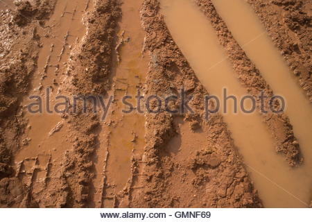 Close up of muddy vehicle and tire tracks filled with water on a construction site, featuring alternating shallow - Stock Photo
