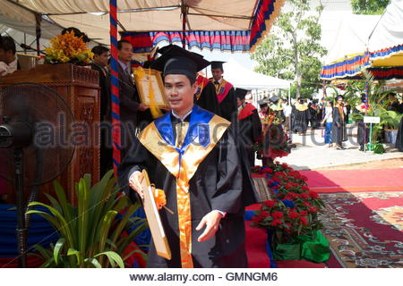 Male university graduate in Asia eagerly carries away his diploma after receiving it at a ceremony. - Stock Photo