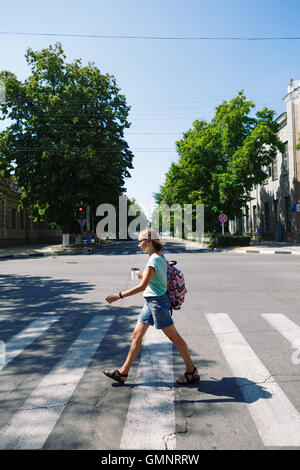 young woman with backpack and coffee crossing the street - Stock Photo