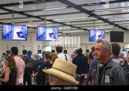 People queuing at the UK border immigration control at Gatwick South Terminal - Stock Photo