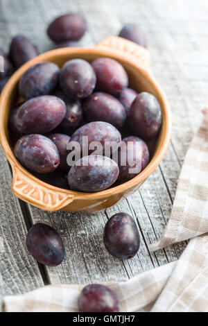 Fresh plums from garden in bowl on old wooden table. - Stock Photo