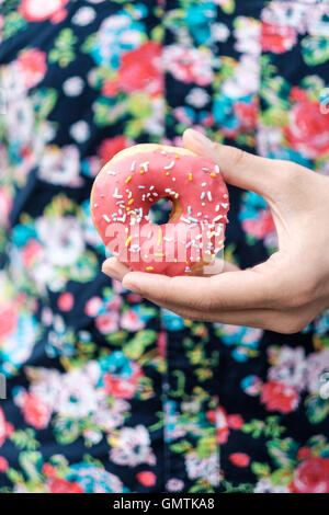 Hand holding a pink sprinkle donut against a floral button up pattern shirt. - Stock Photo