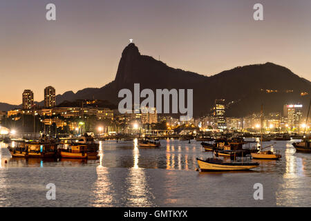Christ the Redeemer statue is lighted at twilight across seen from across Guanabara Bay at the Urca neighborhood - Stock Photo