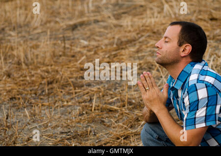 Young man in a plaid shirt praying crouched down in an outdoor field. - Stock Photo