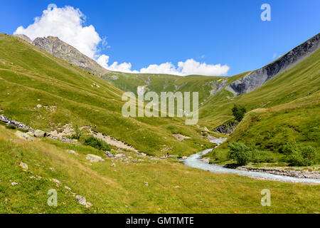 Family resting beside the Ferrand River in the Valley Ferrand, Oisans, France, Europe. - Stock Photo