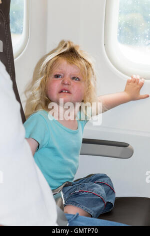 Baby toddler child age two, with tantrum, going on holiday / vacation / flying on Airbus air plane / airplane / - Stock Photo