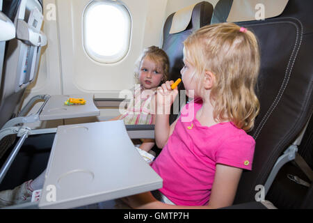 Child / two children age 6 & 4 go on holiday / vacation & eat snack snacking; flying on air plane / airplane / aeroplane - Stock Photo