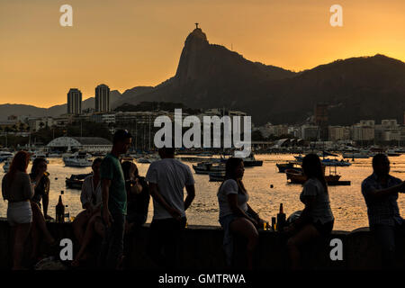 Residents gather to watch the sunset over Christ the Redeemer statue along Guanabara Bay at the Urca neighborhood - Stock Photo