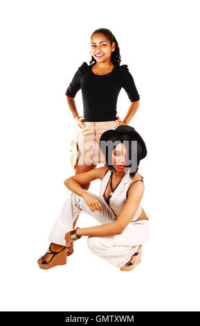 Two lovely mixed race woman posing for white background, one crouching on the floor the other one standing behind. - Stock Photo