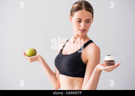 Young woman holding apple and cake - Stock Photo