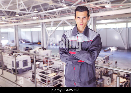 Young worker in uniform standing in CNC factory - Stock Photo