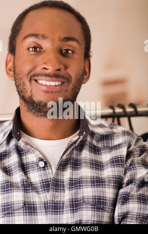Headshot young man smiling to camera, standing in front of clothing rack, fashion concept - Stock Photo
