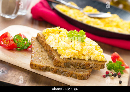 scrambled eggs with chives and herbs and two slices of bread - Stock Photo