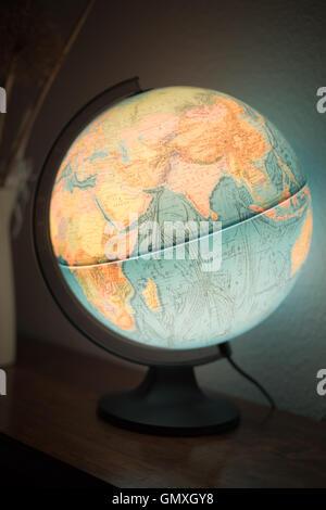 Illuminated Globe on shelf.  Beleuchteter Globus. - Stock Photo