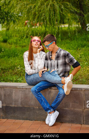 Loving couple teens. Girlfriend and boyfriend together. They wear glasses. First love. He falls in love. Date. - Stock Photo