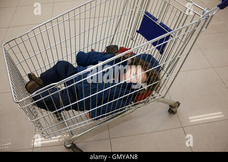 Child in shopping cart - Stock Photo