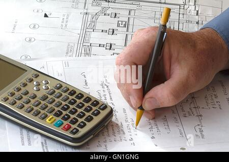 Engineer doing hand calculations on a calculation sheet, with a calculator on the side - Stock Photo