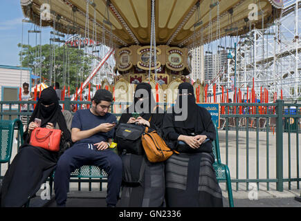 A Muslim family with women in burkas at Luna Park in Coney Island, Brooklyn, New York. - Stock Photo