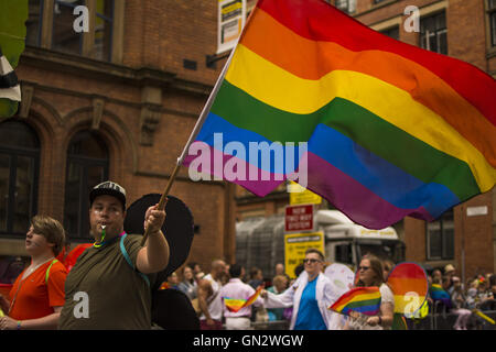 Manchester, UK. 27th August, 2016. Manchester Pride Parade. Man wearing wings waves gay pride flag Credit:  Tom - Stock Photo