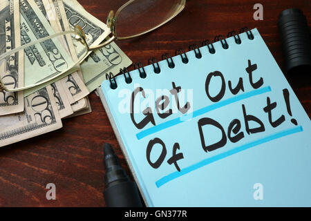 Get out of Debt written on a notepad with marker. - Stock Photo