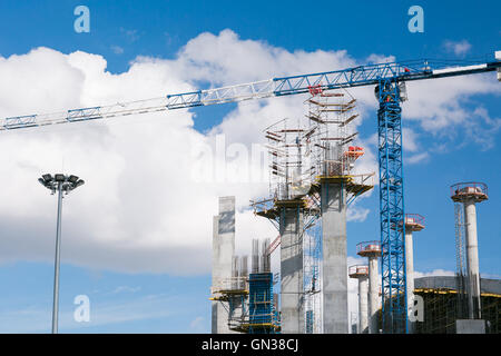 construction company builds a stadium for football competitions. Cranes against a background of the sky. Concrete - Stock Photo