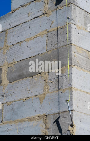 Builder's plumb line hanging against exterior corner wall of house build in progress. In Louth, Linc - Stock Photo