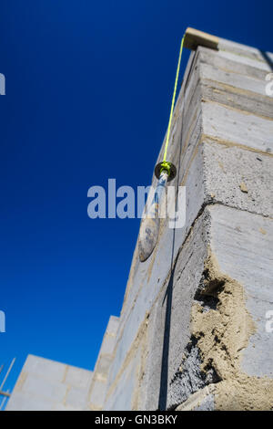 Builder's plumb line hanging against exterior corner wall of house build in progress. - Stock Photo