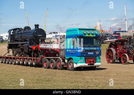 Steam locomotive on back of lorry at Blandford Steam fair - Stock Photo