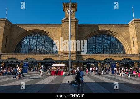 Commuters and Londoners enjoying the late afternoon sun outside King's Cross railway and tube station. - Stock Photo