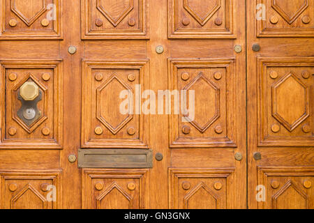 Close view of an elegantly carved light brown wooden door with square pattern and an octagonal door knob on the - Stock Photo