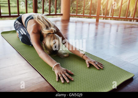 Young woman doing stretching workout on fitness mat. Female performing yoga on exercise mat at gym. Child Pose, - Stock Photo