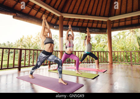 Full length shot of three young women doing the warrior pose in fitness class. Group of young people doing yoga - Stock Photo