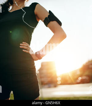 Cropped shot of fit woman standing outdoors with her hands on hips. Female runner wearing smartwatch device with - Stock Photo