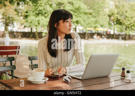 Young woman using laptop and mobile phone at outdoor coffee shop. Asian female sitting at cafe table and looking - Stock Photo