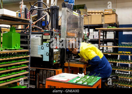 workmen finishing and polishing metal and plastic components ahead of further processing. - Stock Photo