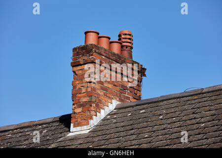old victorian chimney stack with pots on the roof of a row of terraced houses against a blue sky in the uk - Stock Photo