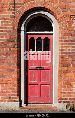 peeling red paintwork in a wooden door in an arched doorway of red brick victorian two up two down house in the - Stock Photo