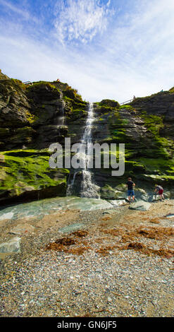 A waterfall flows onto the beach beneath Tintagel Castle in Cornwall, UK - Stock Photo
