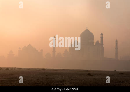 The raising sun in the early morning mist over the Taj Mahal in Agra,Uttar Pradesh. India - Stock Photo