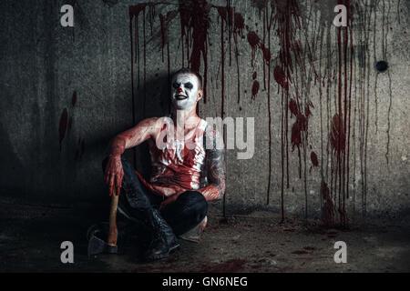 Bloody clown-maniac with ax - Stock Photo