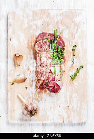 Raw roastbeef meat cut with rosemary, thyme and garlic, vertical - Stock Photo