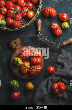 Fresh colorful ripe heirloom tomatoes in basket and wooden board - Stock Photo