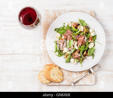 Prosciutto, arugula, figs salad with baguette slices and wine - Stock Photo